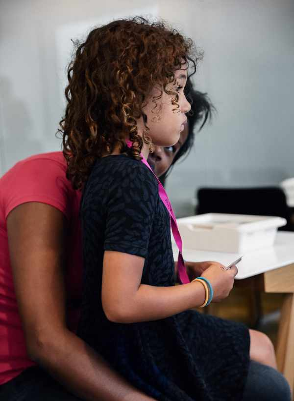 A studious child sits on a woman's lap.